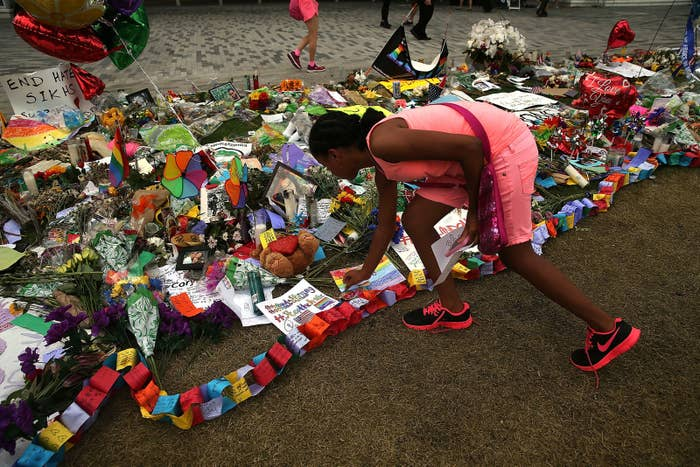 A woman places a note on a memorial for those killed at the Pulse nightclub.