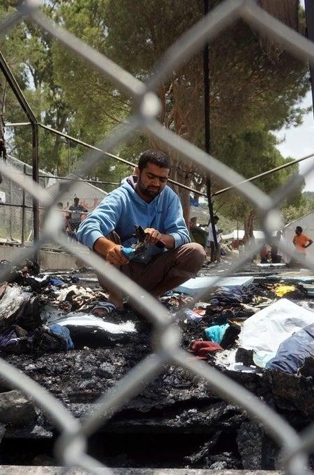 Refugees survey the damage after a riot.