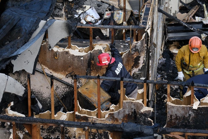 Arson investigators examine the burned-out ruins of an abandoned office building in the Westlake district just west of downtown Los Angeles.
