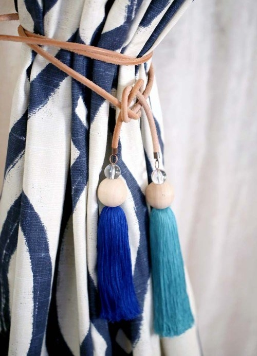 Tie back your curtains with bright tassels on a leather cord.