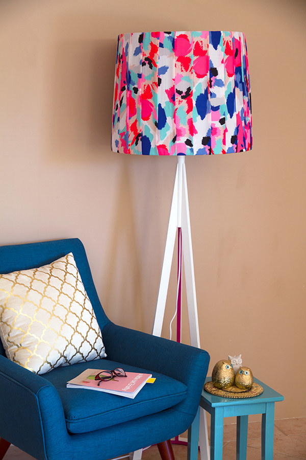 Recover a plain and boring lampshade with strips of bright fabric.