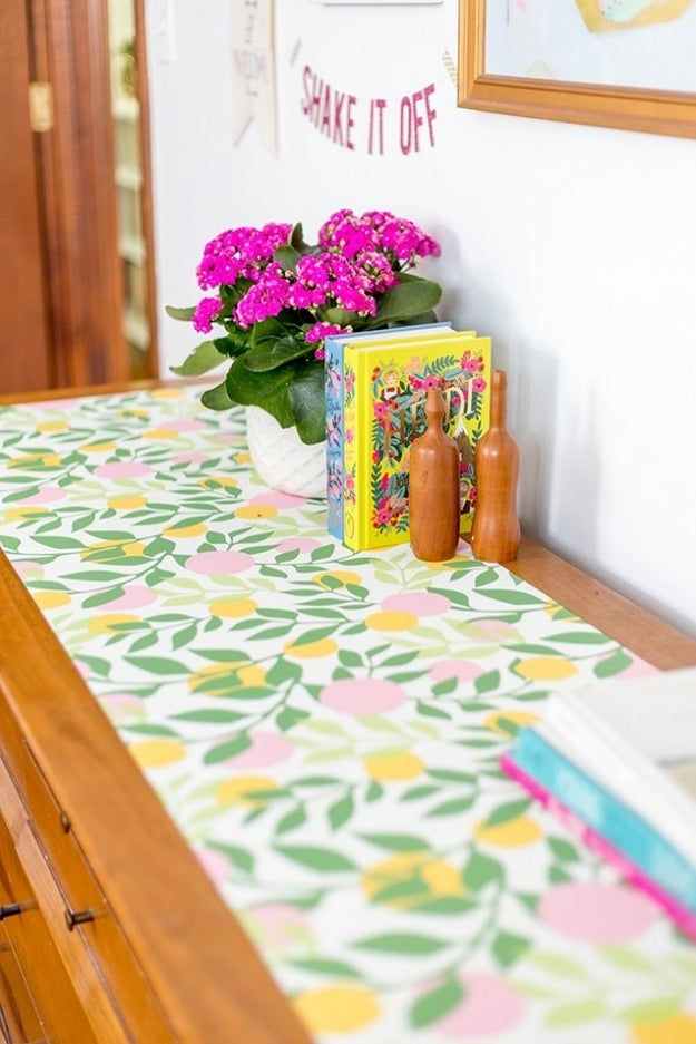 Embellish the top of your dresser with colorful wallpaper (and a few of your favorite books).