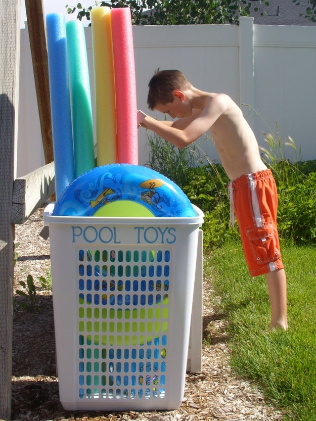 Use a big laundry hamper to corral oversize pool toys.