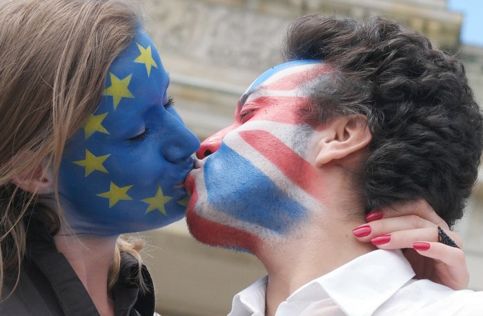 A couple with their faces painted in the flags of the European Union and Great Britain kiss in front of the Brandenburg Gate in Berlin.