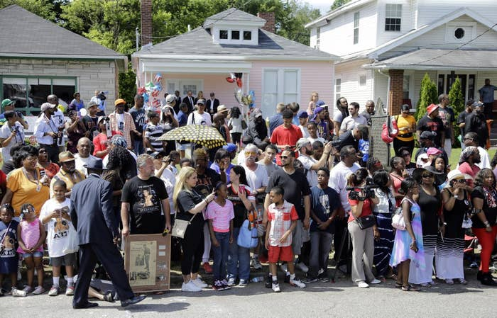 People line the street in front of Muhammad Ali's boyhood home (center) awaiting Ali's funeral procession on June 10 in Louisville.