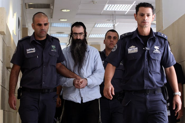 Shlissel is escorted by policemen into the courtroom on Sunday.