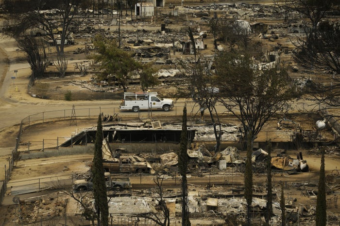 A pickup truck passes by the remains of mobile homes devastated by a wildfire, Saturday in South Lake, California.
