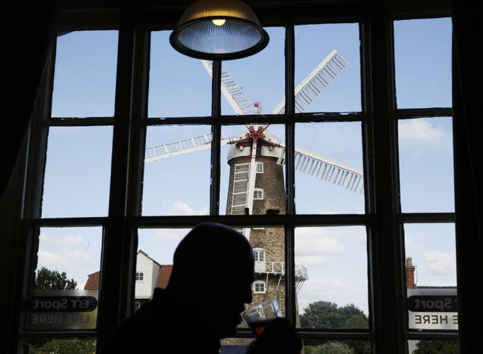 A man who voted Leave drinks a pint in front of the Maud Foster mill in Boston, Lincolnshire.