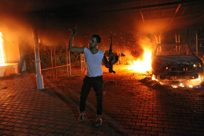 An armed man waves his rifle as buildings and cars are engulfed in flames after being set on fire inside the U.S. Consulate compound in Benghazi on September 11, 2012.