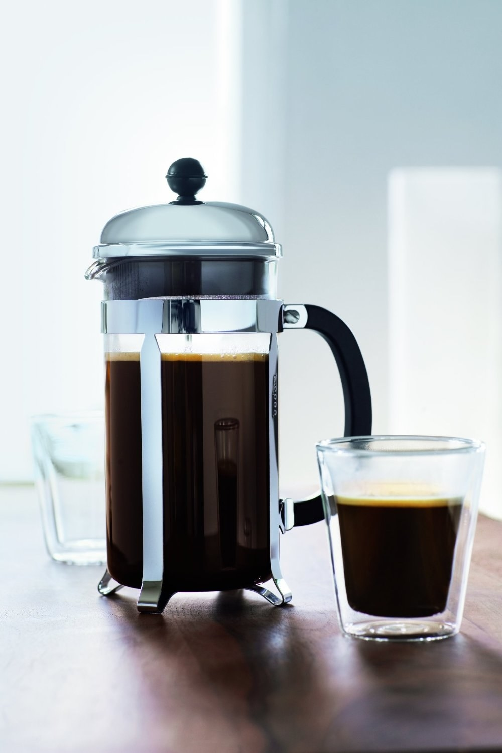 the French press next to a cup of coffee