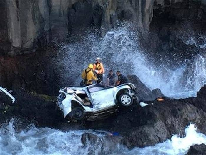 Rescuers work to extricate two women who were in an SUV that drove off a cliff on May 29 in Maui.