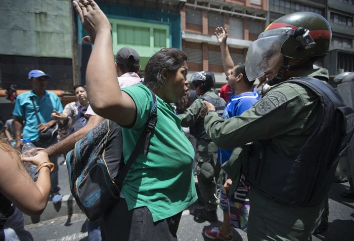 A woman confronts a National Guard soldier during a protest demanding food, a few blocks from Miraflores presidential palace in Caracas.