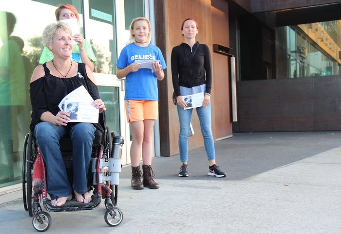 CSUN lecturer Ellen Stohl (left), who sustained a spinal cord injury as a teenager and uses a wheelchair, protests outside a screening of Me Before You in Los Angeles. She and other activists were kicked out of the box office area of The Landmark.