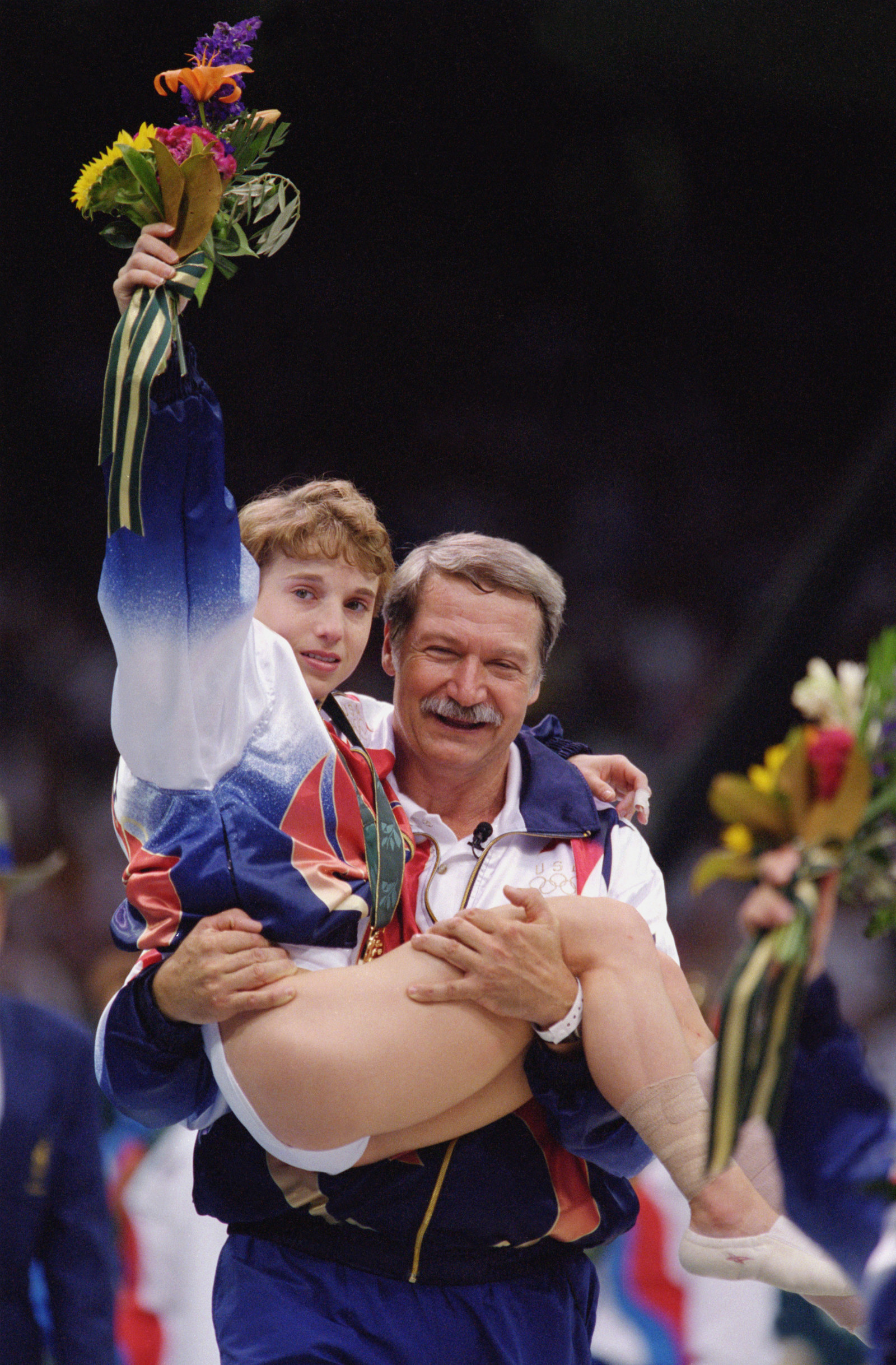 Kerri Strug being carried off the floor by her couch