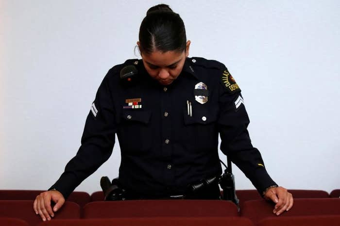 A Dallas police officer bows her head at the Joy Tabernacle A.M.E. church during Sunday service.