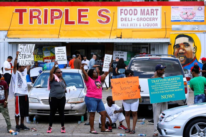Protesters demonstrate outside the Triple S Food Mart where Alton Sterling was shot in Baton Rouge.