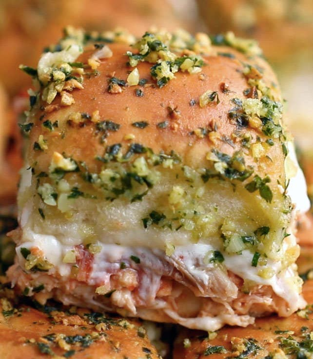 Servings: 12INGREDIENTS12-pack of dinner rolls or Hawaiian sweet rolls3 cups rotisserie chicken½ cup marinara sauce8 ounces fresh mozzarella, sliced¼ cup basil, chopped½ cup melted butter3 cloves garlic, finely chopped2 tablespoons basil, finely chopped2 tablespoons grated parmesanPREPARATION1. Preheat oven to 350°F/175°C.2. Slice the rolls in half lengthwise.3. Place the bottom half on a 9x13 baking tray.4. Spread the chicken evenly on the rolls, followed by the marinara, mozzarella, and basil.5. Place the remaining half of the rolls on top.6. Mix the melted butter with the garlic, parsley, and parmesan.7. Brush the top of the rolls with the butter mixture.8. Bake for 20 minutes.9. Slice, then serve!