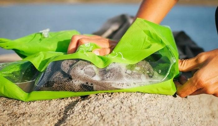 Esta ligera bolsa usa las funciones de una tabla de lavar para hacer una lavadora portátil que te permite lavar tu ropa en cualquier momento y lugar.
