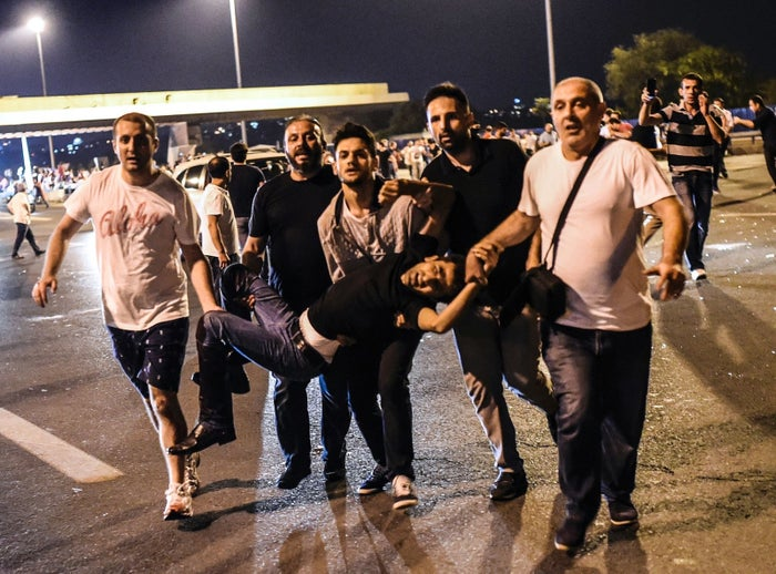 A man shot during a clash with the military is carried by people near Bosphorus bridge in Istanbul.