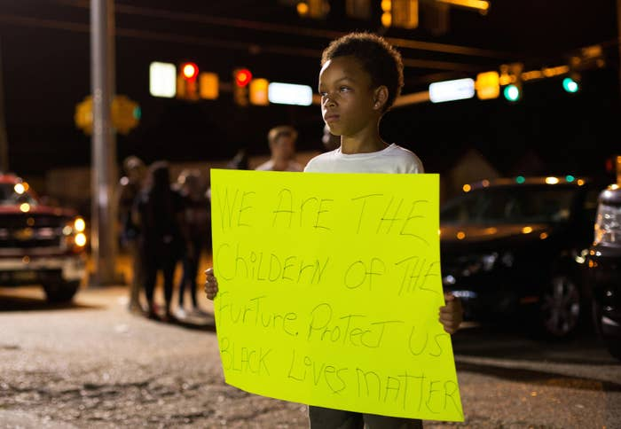 Terrance Anderson holds a placard outside the Triple S Food Mart where Alton Sterling was shot dead by police in Baton Rouge.