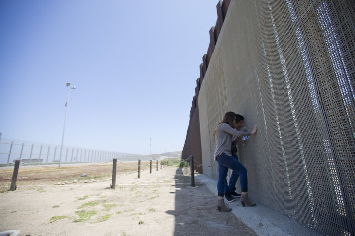 Eva Lara and her brother talk through a border fence in San Diego to their grandmother, Juana Lara, who stands on the Mexican side.