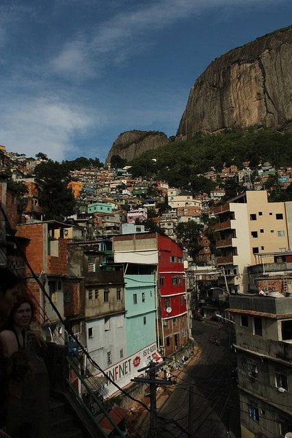 "If you type ""favela"" into Google Translate, the resulting word is ""slum"" or ""shanty town"". The word favela comes from a plant that grows in the Northeast of Brazil. When the first favela was founded in the late 1800's, it was named ""Favela Hill"" after the plant. Today, that favela still exists and is called Providência, in Rio's Port region. The only reason we use ""slum"" as a translation for ""favela"" is to find an easy way to relate it to something familiar in our own cities. Unfortunately, this translation brings connotations of poverty, precariousness and lack of safety. While some favelas have ""slum-like"" conditions, it is incorrect to generalize that favelas are slums because many of them have sturdy homes, commerce, and middle-class residents."