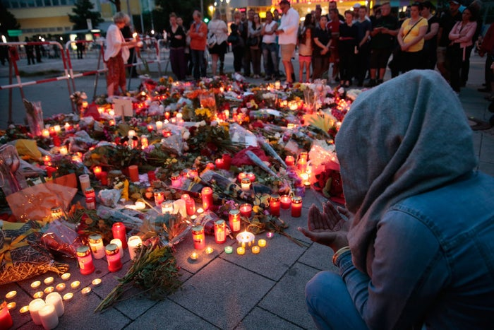 People mourn at memorials to the OEZ shopping center victims near the scene of the shooting.