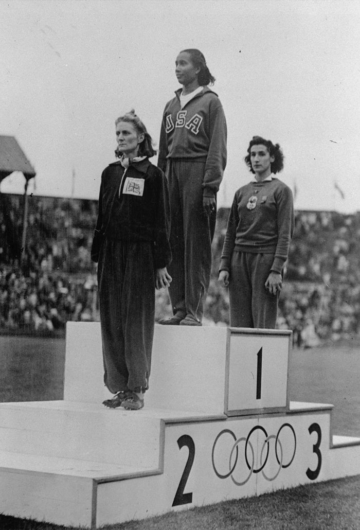 Pictured here on the winner's section of the Olympic podium at Wembley Stadium in the United Kingdom, Alice Coachman was the first black woman to win an Olympic gold medal. On August 7, 1948, the track and field athlete earned the gold for winning the women's high jump.