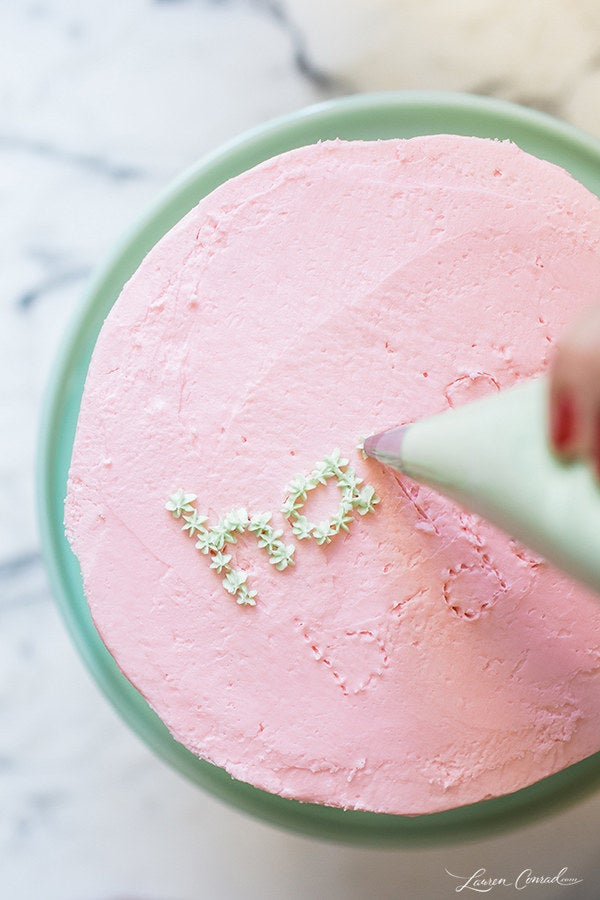 """It gives you a little template, and you can easily """"erase"""" any mistakes by smoothing the icing back out. Then, to make it even easier, fill out the text with small stars instead of trying to write out the letters like you would with a pen. Here's the tutorial. And check out 28 other ways to easily decorate a cake here."""
