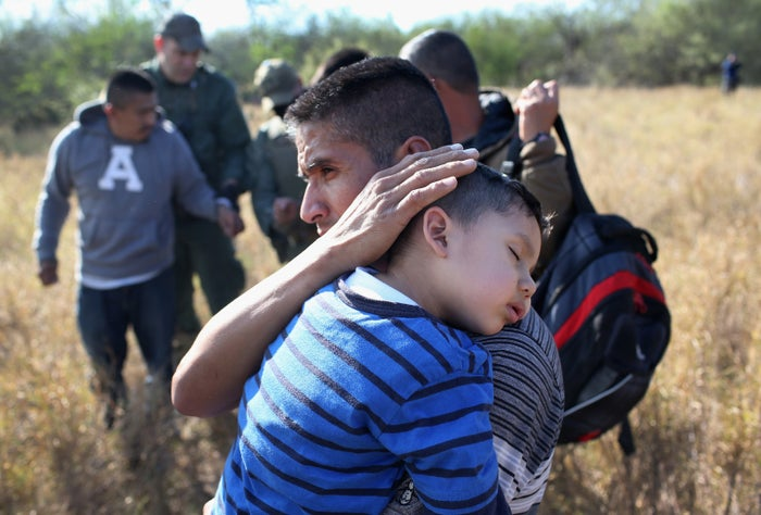 A father holds his sleeping son, 3, after they and other undocumented immigrants were detained by Border Patrol agents near Rio Grande City, Texas.
