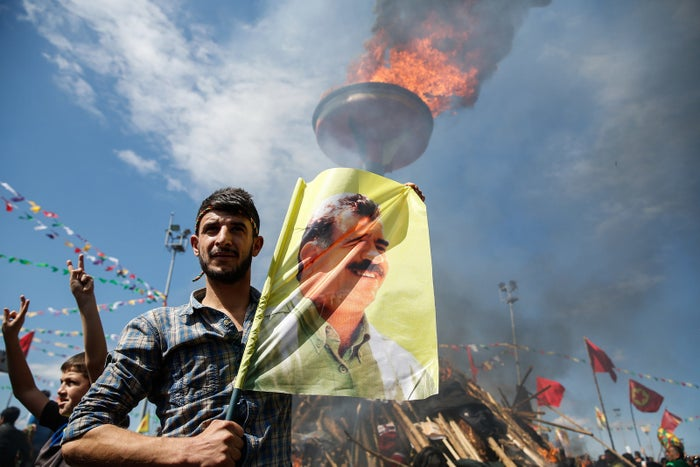 A Kurdish man holds a flag with a picture of PKK leader Abdullah Ocalan.