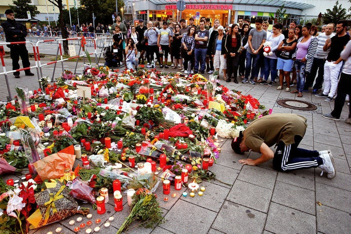 A man prays beside flowers laid in front of the Olympia shopping mall, where an 18-year-old German-Iranian gunman killed nine people on a shooting rampage.