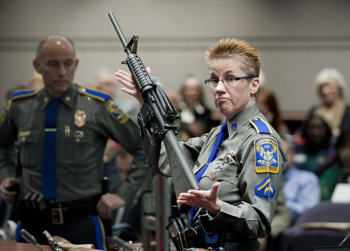 Barbara J. Mattson, of the Connecticut State Police, holds up a Bushmaster AR-15 rifle.