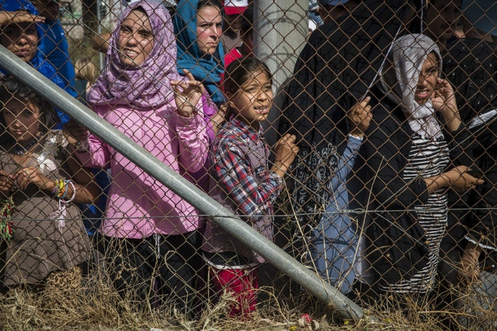 Women from Afghanistan, Syria and Iraq are made to wait behind a fence during the visit of UN Secretary General Ban Ki-Moon to Kara Tepe Camp in Lesvos, Greece, June 18, 2016.