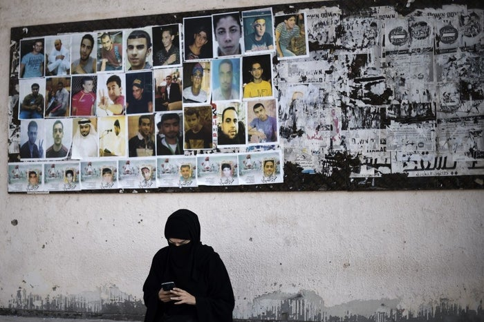 A Bahraini woman sits near portraits of jailed political activists and protesters killed during clashes with police in Sitra, south of Manama, 12 February 2016.