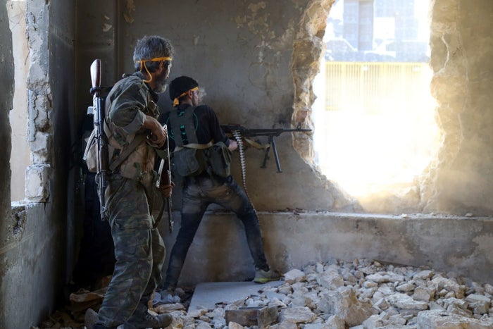 Rebel fighters fire toward regime forces on the southwestern edges of Aleppo.