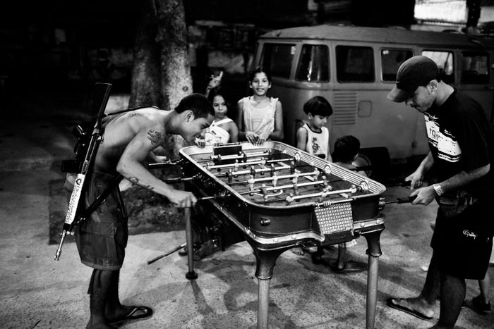 A young drug trafficker plays foosball with another young man in Morro do Dendê in northern Rio, July 2008.