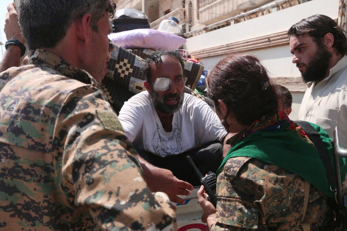 Syria Democratic Forces (SDF) fighters chat with an injured civilian