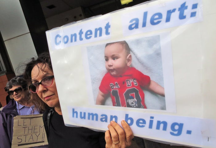 A woman holds up a placard at a protest outside an immigration office in Sydney.