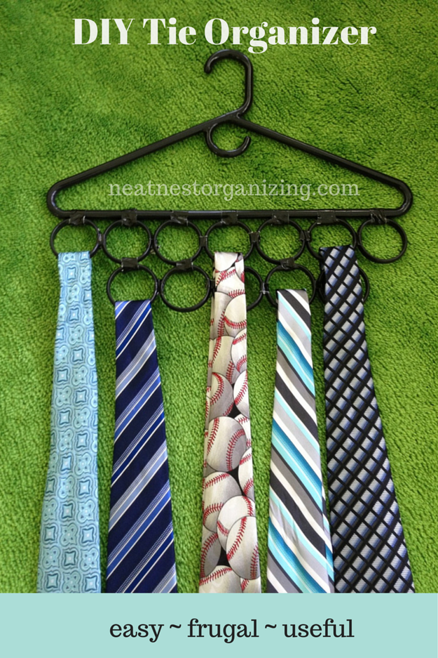 Duct tape shower curtain rings to a hanger to make an affordable and functional tie organizer.