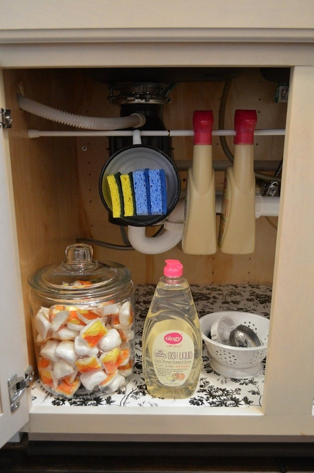 Hang a tension rod beneath your kitchen sink to store sponges and spray bottles as needed.