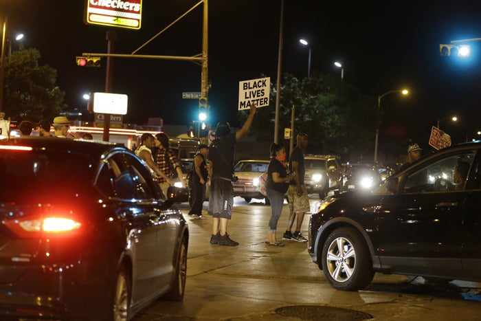 Protesters block traffic Sunday at a busy intersection in Milwaukee.