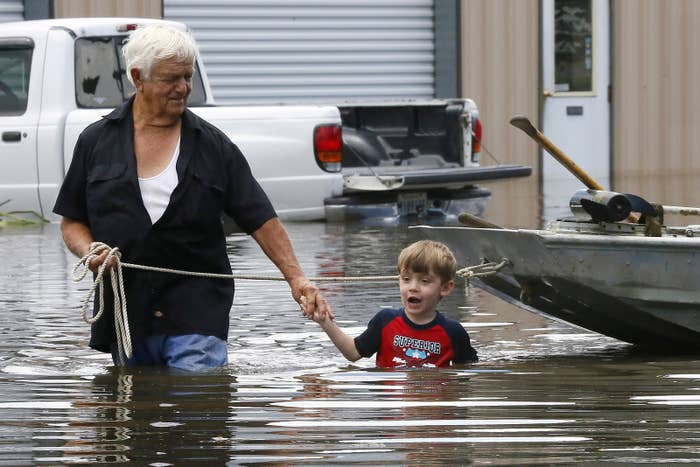 Richard Rossi and his 4 year old great grandson Justice wade through water in search of higher ground after their home took in water in St. Amant, Louisiana, Aug. 15, 2016.