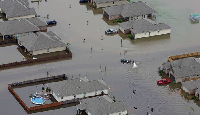 In this aerial photo a boat motors between flooded homes after heavy rains inundating the region, Aug. 13, 2016, in Hammond, La.