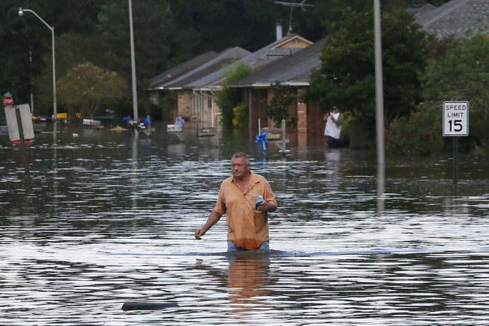 A man wades through a flooded street Monday in Ascension Parish, Louisiana.