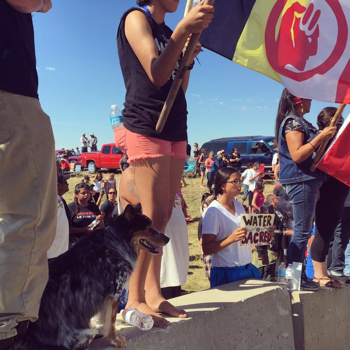 "Protesters stand at the front barricades of the protest zone, holding signs that read ""Water is sacred"" and ""Mni Wiconi"" (""Water is life"" in Lakota)."