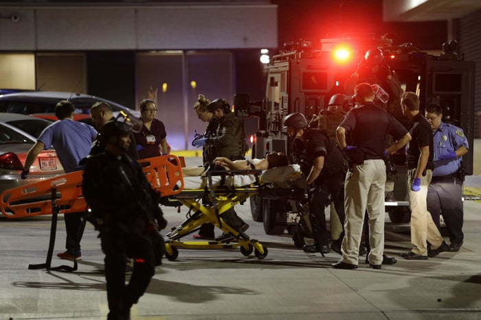Under armed police personnel a young man is rushed into a hospital in Milwaukee, Sunday.