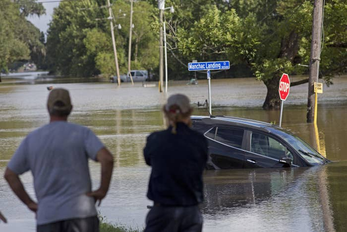 Residents survey the floodwaters Tuesday on Old Jefferson Highway at Bayou Manchac in Prairieville.