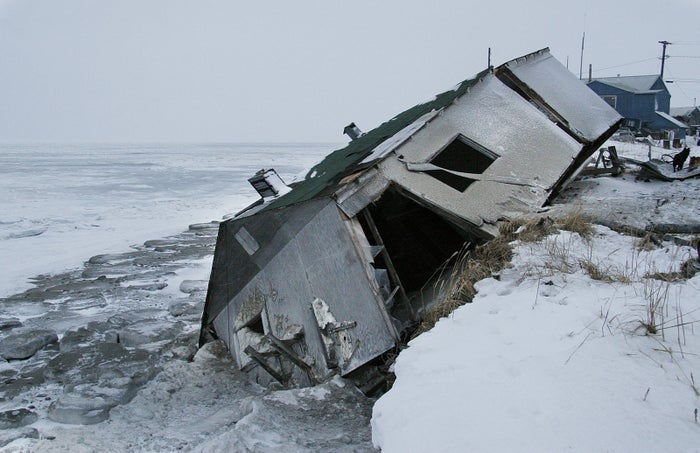 An abandoned house at the west end of Shishmaref, Alaska after sliding into the beach during a storm in 2005.