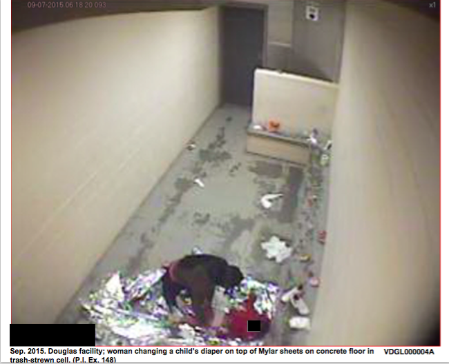 In one image ordered released by the judge, a woman changes a baby's diaper on top of a Mylar sheet.